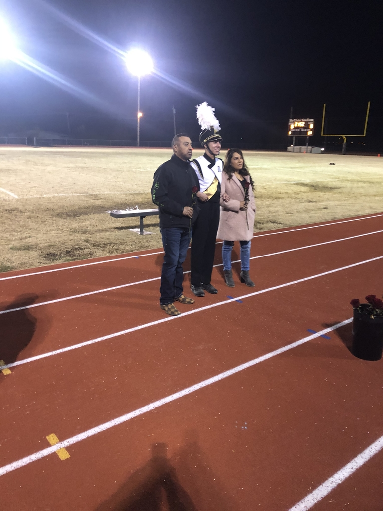 Kevin Robles passing with has parents at senior night.